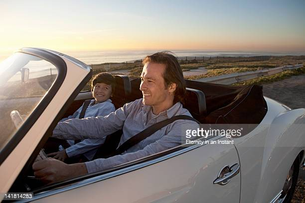 Father and son enjoying drive by ocean