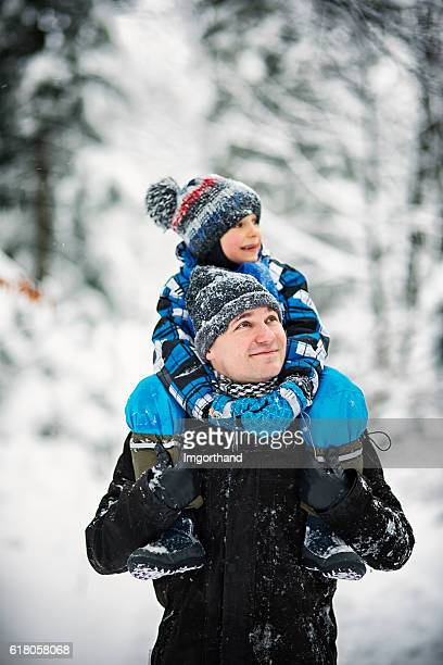 Father and son enjoying winter walk in forest.