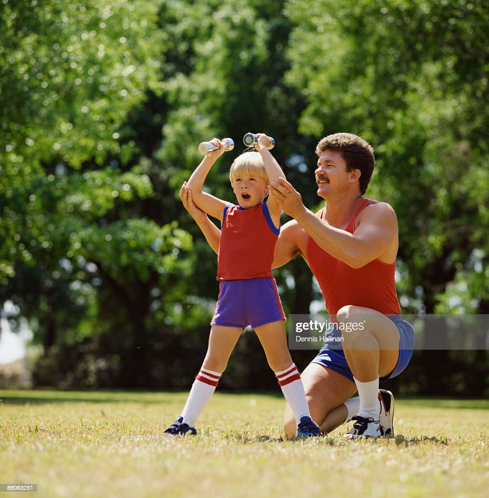 Father and son exercising at the park : Stock Photo