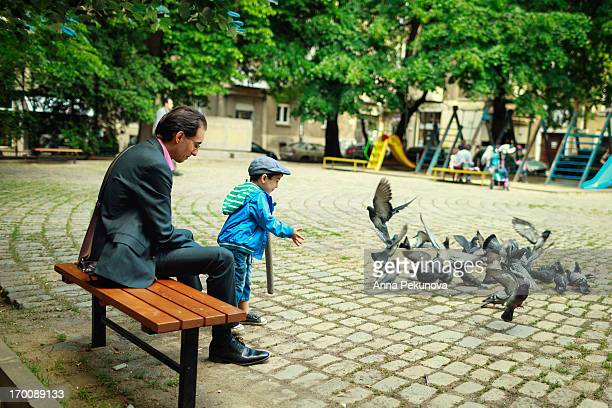 Father and son feeding pigeons