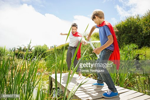 Father and son (6-7) fighting with wooden swords on pier : Stock Photo