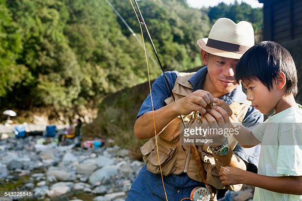 Father and son fishing by a stream.