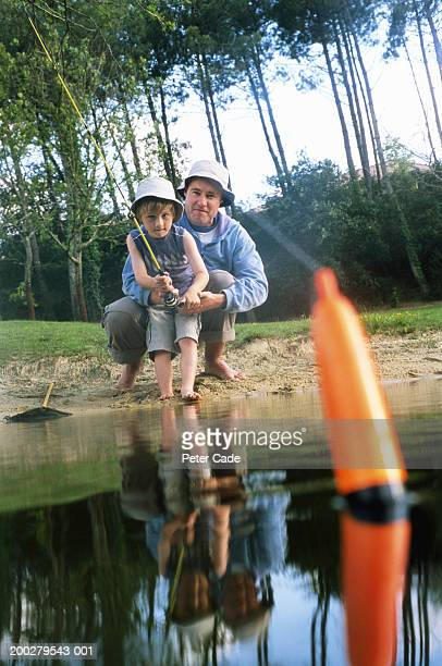 Father and son (4-6) fishing in lake