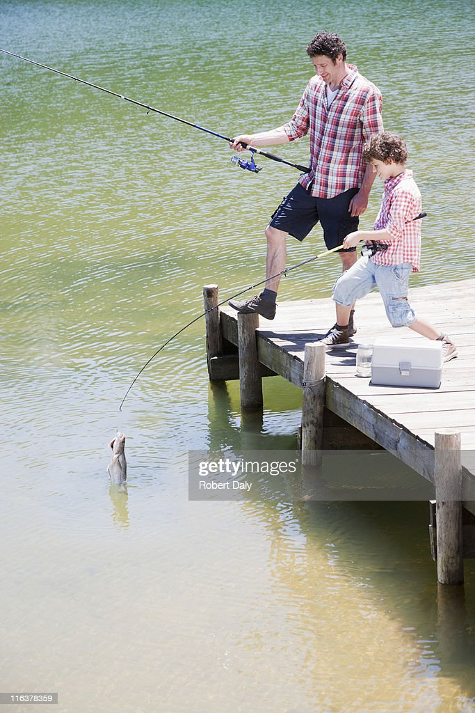 Father and son fishing off dock : Stock Photo