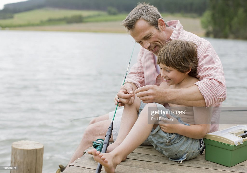 Father and son fishing off pier at lake : Stock Photo