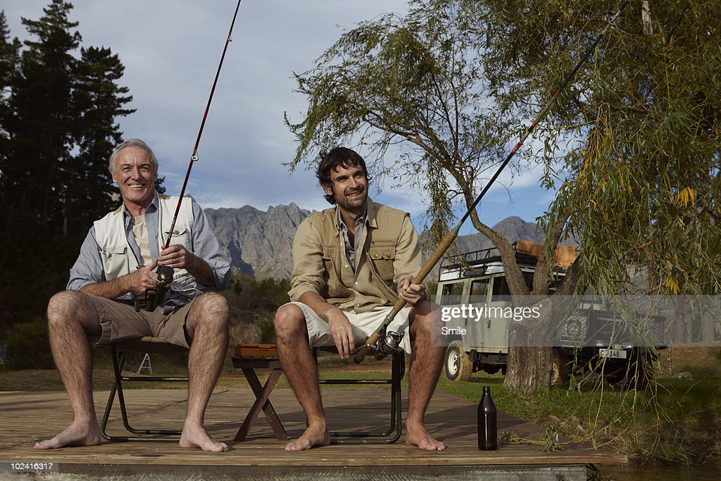 Father and son fishing on jetty : Stock Photo