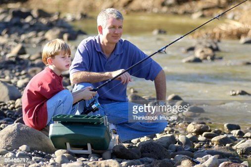 Father and son fishing on river rocks stock photo getty for What age do you need a fishing license