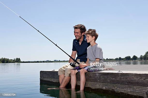 Father and son fishing together on dock