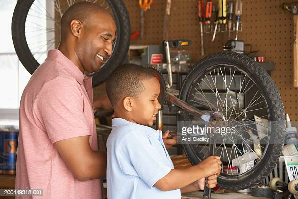 Father and son (57) fixing bicycle in garage