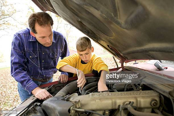 Father and son fixing car engine