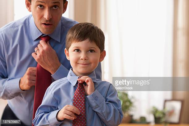 Father and son fixing ties together