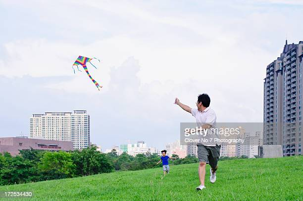 Father and son fly a kite.