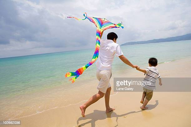 Father and son flying a kite at the beach