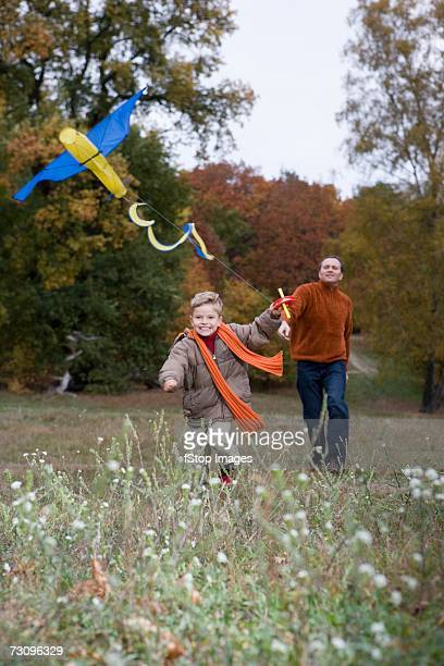Father and son flying kite in autumn