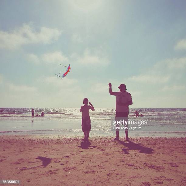 Father And Son Flying Kite On Sunny Beach Day