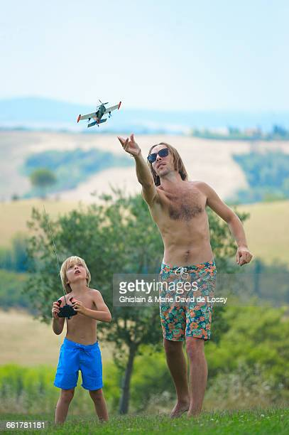 Father and son flying remote control plane, outdoors