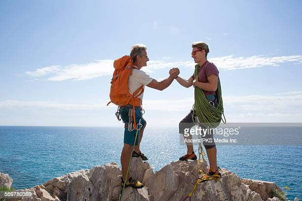 Father and son grasp hands at summit of climb