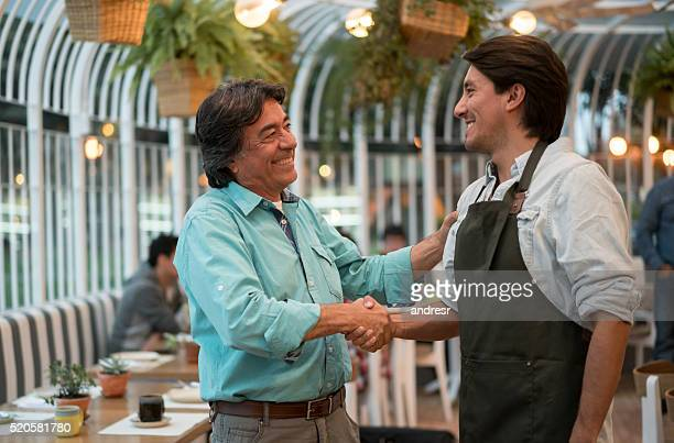 Father and son handshaking at a restaurant