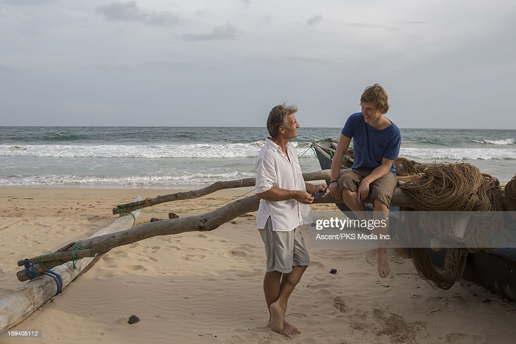 Father and son have conversation on fishing boat : Stock Photo