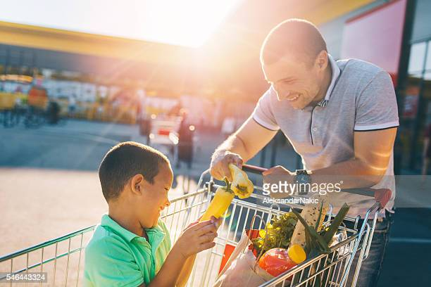 Father and son having fun after grocery shopping