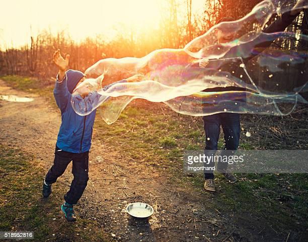 Père et fils s'amuser avec des bulles sur printemps en soirée