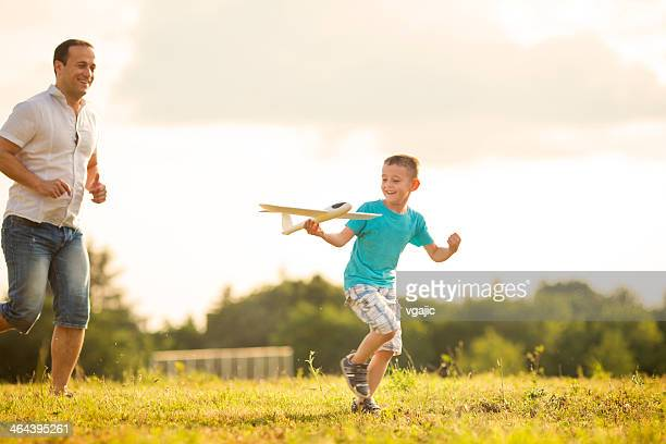Father and son Having Fun With Toy Airplane Outdoors.