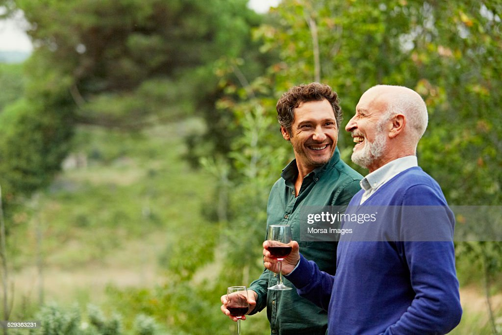 Father and son having red wine in park