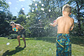 Father and son (6-7) having water fight