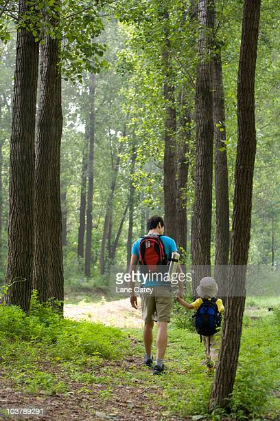 Father and son hiking through the forest