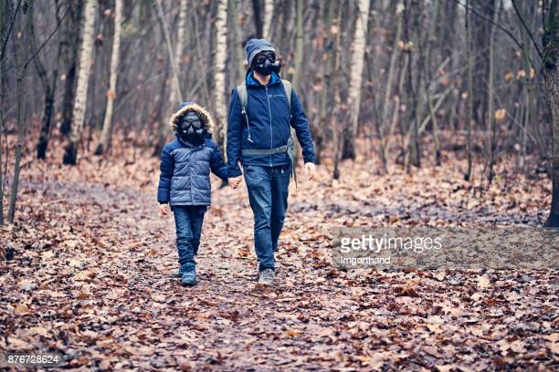 Father and son hking in polluted forest