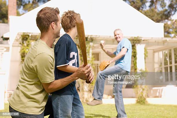 Father and son holding a baseball bat, grandfather pitching