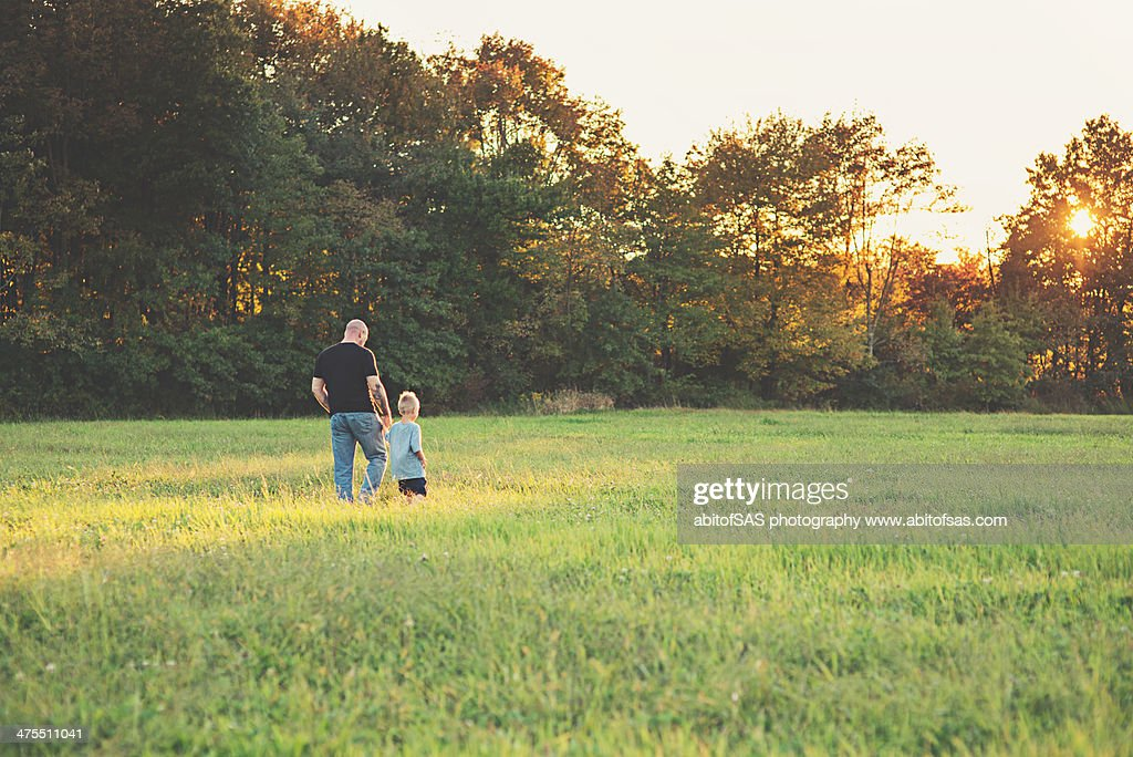 Father and son holding hands in a field