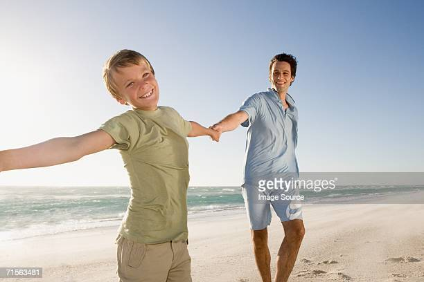 Father and son holding hands on the beach
