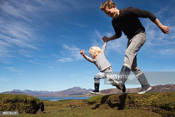 Father and son holding hands running, Isle of Skye, Hebrides, Scotland