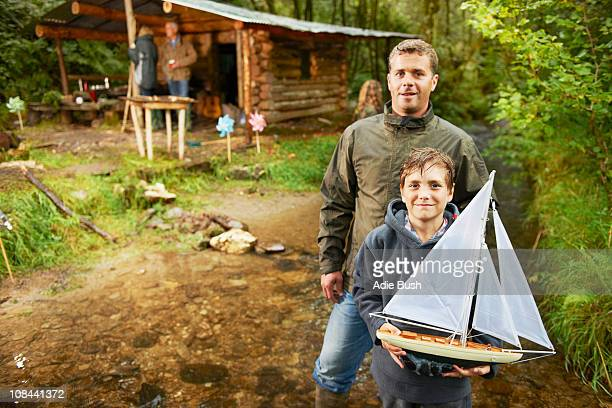 Father and son holding sailing boat