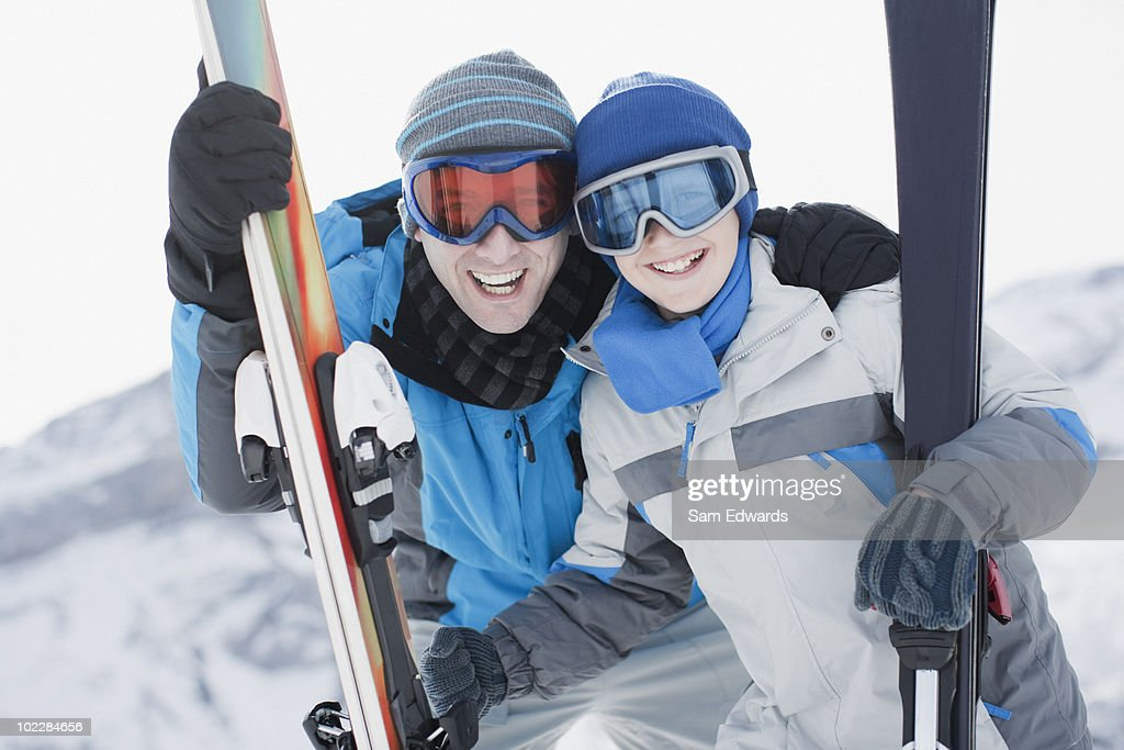 Father and son holding skis : Stock Photo