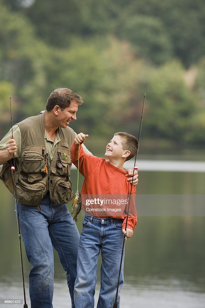 Father and son holding up a fish : Stock Photo