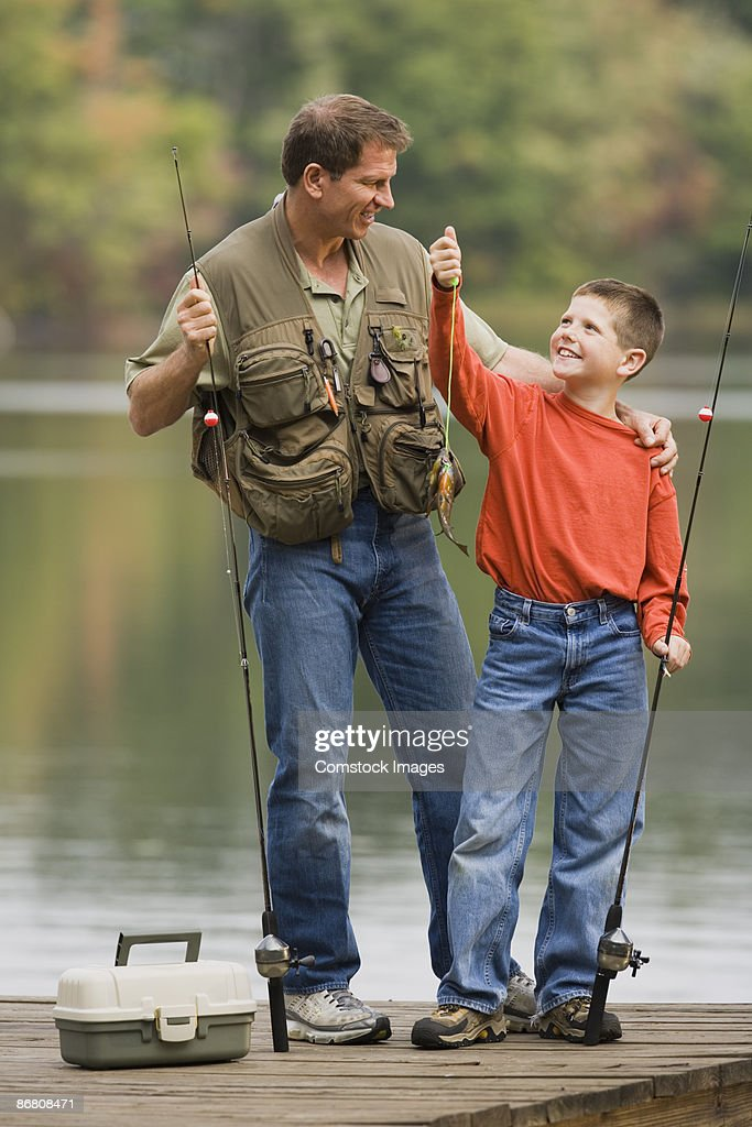 Father and son holding up a fish