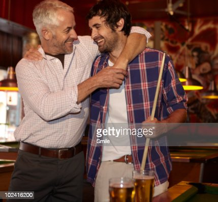 Father and son hugging each other, laughing : Stock Photo