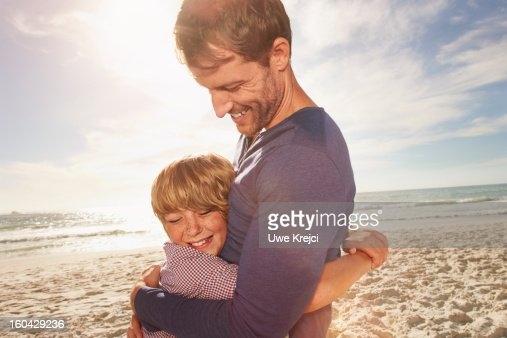 Father and son (6-8) hugging outdoors : Stock Photo