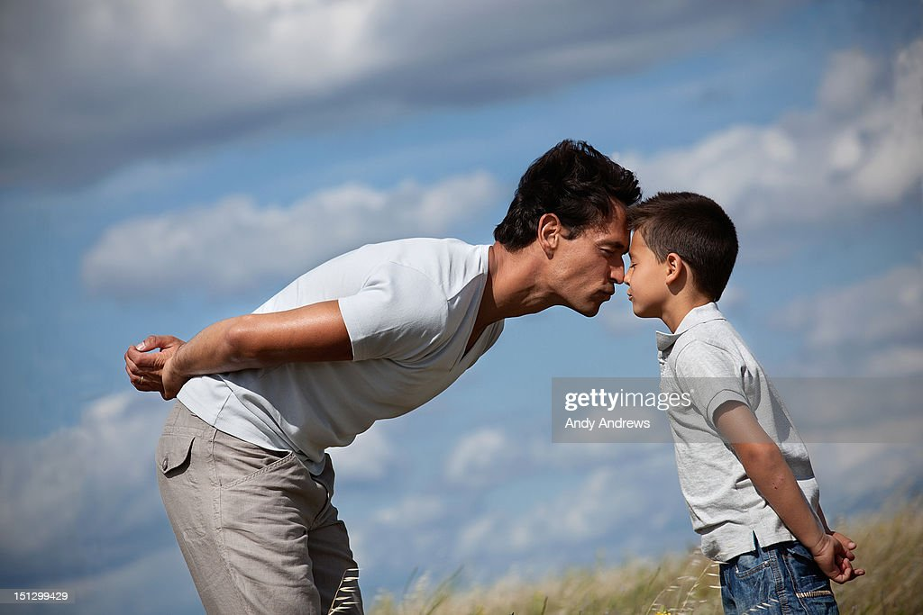 Father and son in a field showing affection : Stock Photo
