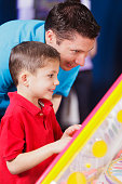 A father helps his son play a game in an amusement arcade.