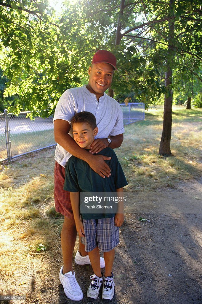 Father and son (8-10) in backyard : Stock Photo
