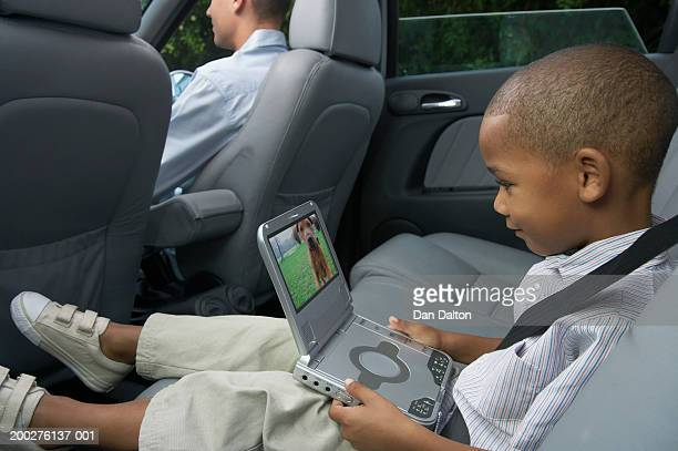 Father and son (5-7) in car (focus on boy using portable DVD player)