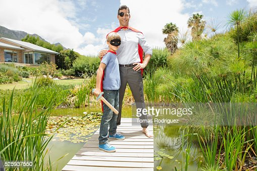 Father and son (6-7) in costumes standing on pier : Foto stock