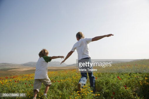 Father and son (8-10) in field, playing aeroplanes, rear view : Stock Photo