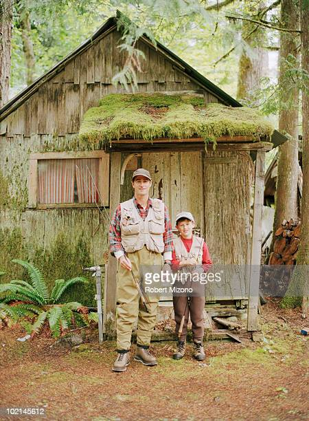Father and son in front of cabin