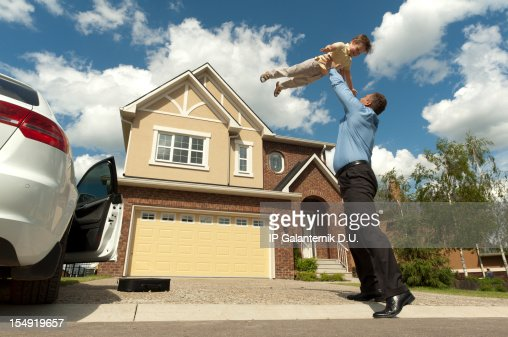Father and son in front of their new suburban house