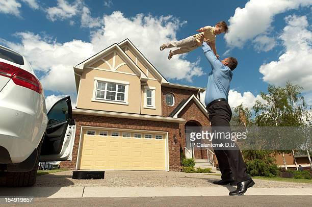 Padre e hijo delante de casa suburbana su nuevo
