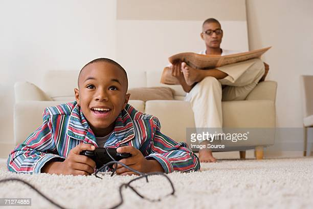 Father and son in lounge, son playing video game